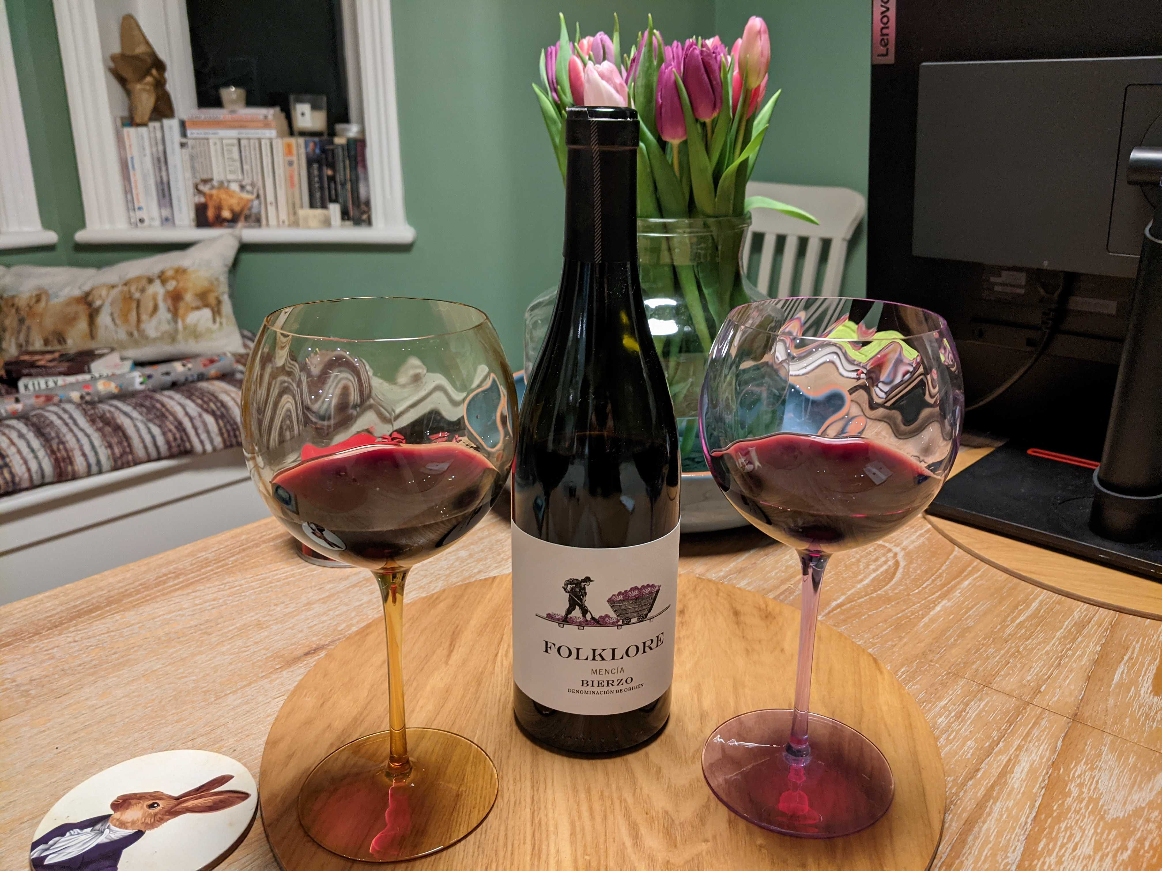 "Photograph of a couple of glasses of ""Folklore"" wine, along with the bottle"